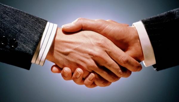 duas pessoas se cumprimentando, fechado um acordo entre elas, paletó cinza com botões pretos, um com camisa branca e listras cinzas e outro com camisa branca, imagem com fundo cinza