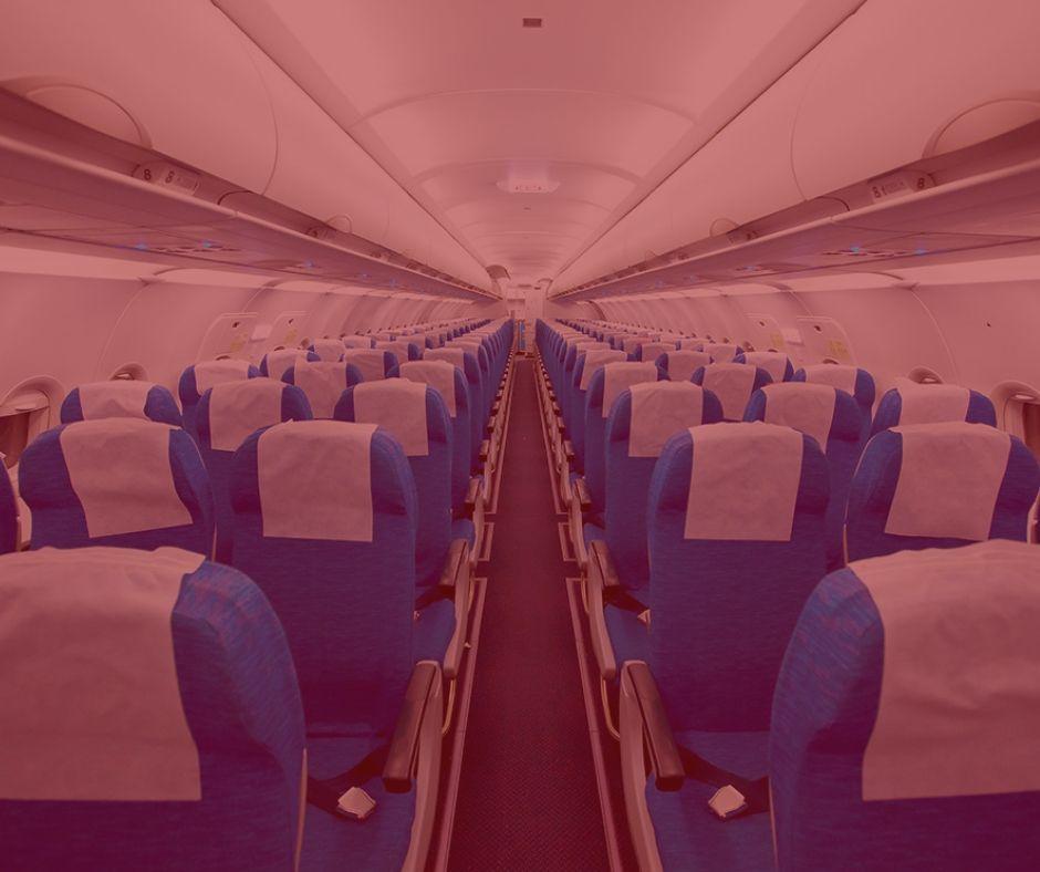 imagem com fundo vermelho, da parte de dentro de um avião. Bancos nas cores azul, com o encosto com panos brancos, teto do avião é branco. Imagem simboliza ação da Gol com a cervejaria Brahma que o Procon está investigando.