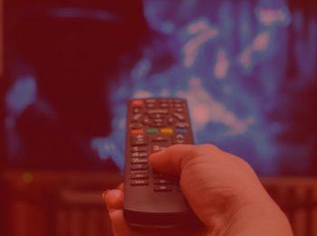 imagem simbolizando o direito do consumidor, uma pessoa segurando um controle remoto apontado para uma televisão, que esta com uma imagem no tom azul. Imagem com fundo vermelho.