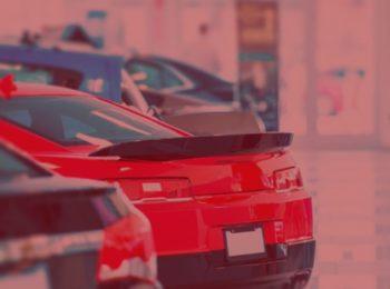 imagem com fundo vermelho, simbolizando a notícia de Fábrica de veículos ressarcirá consumidora por carro vendido com propaganda enganosa em Brusque, imagem com carros, camaro, cruze, fotos da concessionária.