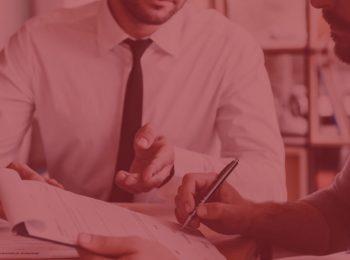imagem simbolizando a rescisão indireta. Imagem com fundo vermelho, duas pessoas conversando e uma assinando um documento. Homem com camisa branca e gravata preta. Artigo rescisão indireta.