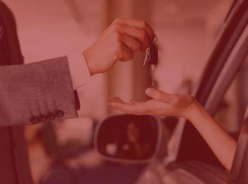 """imagem com fundo vermelho. Simbolizando notícia """" Vendeu seu veículo ? Se vender, transfira o documento. """" com duas pessoas efetivando a compra do carro, homem com terno cinza segurando a chave e passando para o novo comprador."""