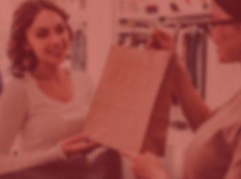 imagem com fundo vermelho. Foto traz a notícia: Direito do consumidor: produtos de mostruário têm garantia e direito à troca, sim! Foto com pessoa realizando a troca de uma mercadoria, sacola marrom, uma das pessoas esta vestindo uma camiseta regata na cor branca.