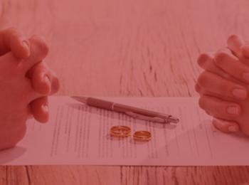 Imagem com fundo vermelho. Simbolizando o Divórcio Extrajudicial, duas pessoas se divorciando, com suas alianças em cima da mesa, alianças douradas. Há um papel em cima da mesa, e uma caneta.