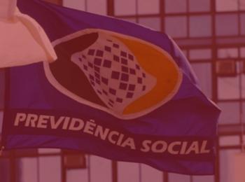 imagem com fundo vermelho. Artigo que traz os Principais pontos da Reforma da Previdência Social. Imagem com a bandeira da previdencia social, bandeira azul, verde, azul a amarela. Há também um prédio ao fundo.