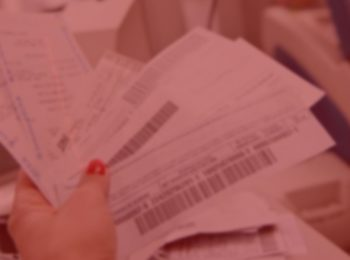imagem com fundo vermelho. Que traz a notícia de Lei garante que consumidor possa escolher data do vencimento de suas contas. Mulher com unha pintada de vermelho segurando alguns boleto para serem pagos.