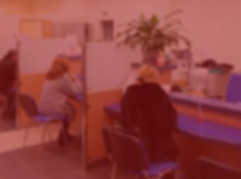 imagem com fundo vermelho, trazendo a seguinte noticia; Banco deve indenizar funcionária discriminada por causa da idade. Pessoas sentadas numa cadeira de banco, cadeiras e forros azuis. Pessoas trajando roupas pretas e cinzas.