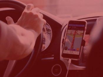 imagem com fundo vermelho. Homem, motorista de aplicativo, dirigindo com o gps ligado, indicando uma direção para seguir. Volante preto, console prata. Imagem traz notícia de Uber terá de indenizar passageiros após motorista levar pertences.