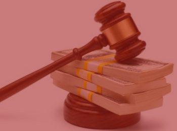 Imagem com fundo vermelho. Artigo: Assistência judiciária e gratuidade na Justiça do Trabalho. Martelo de justiça na cor marrom, sob algumas notas de dinheiro verde.