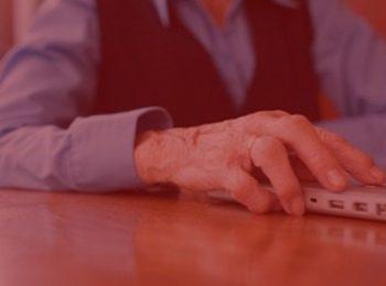 imagem com fundo vermelho. Notícia: Serasa deve indenizar idosa que teve direito à informação negado. Idosa mexendo no computador, usando um colete preto e uma camisa jeans. Computador na cor cinza.