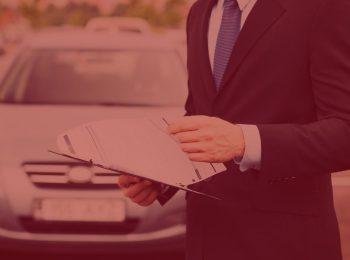 imagem com fundo vermelho. Notícia: Consumidor contemplado em consórcio será indenizado por atraso na entrega do veículo. Foto com um homem vestindo um terno preto, camisa branca e gravata azul, analisando alguns papéis que estão presos a uma prancheta. Ao fundo, um veículo estacionado.