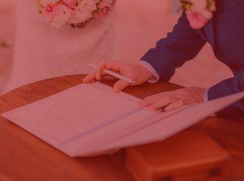 imagem com fundo vermelho. Artigo: A importância do pacto antinupcial. Na foto, duas pessoas assinando acordo de casamento, ela vestida de noiva com um vestido branco, ele vestido de noivo com um terno azul. Acordo esta sendo assinado sob uma mesa de madeira na cor marrom.