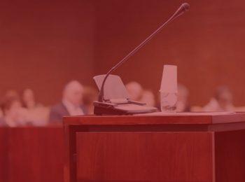imagem com fundo vermelho. Notícia: Amizade real comprovada em redes sociais invalida depoimento de testemunha. Na foto, um microfone em uma audiência, para ouvir a testemunha.