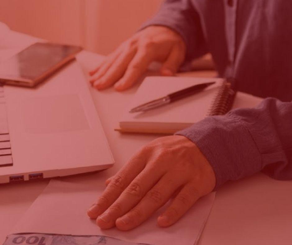imagem com fundo vermelho. Notícia: Pensão alimentícia é alterada em caso de desemprego do pai. Na foto, um homem segurando um envelope com a mão esquerda. Há sobre a mesa, uma agenda com caneta, um celular e um notebook. Homem vestindo uma camisa azul.