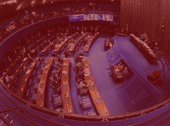 Imagem com fundo vermelho. Notícia: Senado aprova reforma da Previdência em 1º turno. Na foto temos o plenário aonde os senadores realizam a votação da reforma da previdência. Tapete azul e bancada marrom.