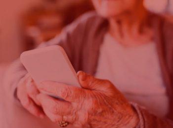 imagem com fundo vermelho. Notícia: Banco indenizará idosa por excesso de ligações de cobrança. Na foto, uma idosa segurando um celular. Cores: brancas, cinza e dourada.