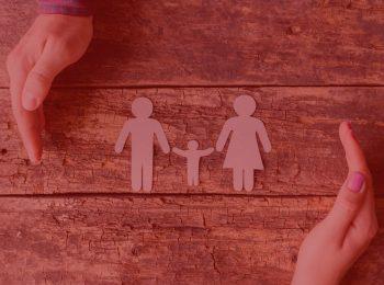 imagem com fundo vermelho. Artigo: O lar de referência na guarda compartilhada. Na foto, duas pessoas com as mãos sob uma mesa de madeira com um recorte de papel simbolizando uma família.