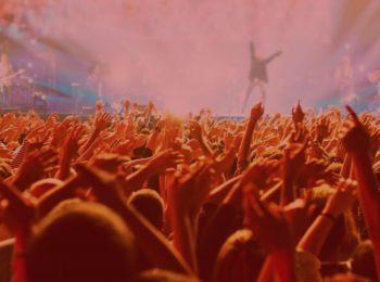 notícia: Casal que perdeu show após horas na fila será indenizado. Na foto, pessoas com as mãos para cima curtindo um show. Cores na imagem; azul e rosa.