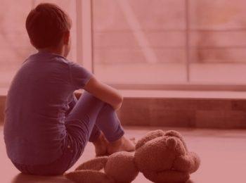 imagem com fundo vermelho. Notícia: Pai indenizará por abandono afetivo. Na imagem uma criança olhando para janela com seu urso ao lado, cores azuis e marrom.