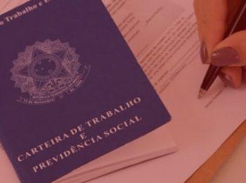 imagem com fundo vermelho. Artigo: Novas regras para o contrato de trabalho. Na foto um carteira de trabalho e a pessoa assinando um contrato de trabalho. Cores na foto: azul, branco, vermelho e roxo.