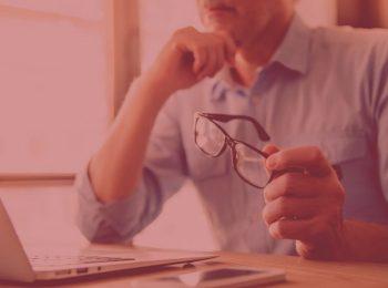 imagem com fundo vermelho. Artigo: Revisão da vida toda: quando é possível? Na foto, um senhor segurando o óculos e olhando para o computador. Cores na foto: cinza, preto, azul, marrom.