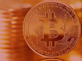Notícia: Empresa gestora de bitcoins terá de indenizar e devolver dinheiro investido. Imagem com fundo vermelho, na foto uma moeda de bitcoins, moeda virtual.