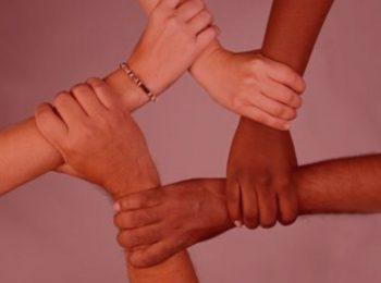 artigo: Injúria racial x racismo. Imagem com fundo vermelho, na foto, 4 braços dando mãos dadas.