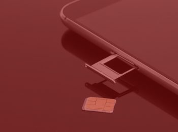 notícia: Tim indenizará cliente que teve chip clonado. imagem com fundo vermelho. Na foto, um celular preto com a gaveta de chip na cor prata aberta e o chip em cima da mesa.
