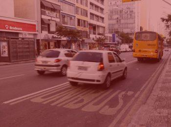 imagem com fundo vermelho. Notícia: Consumidor deve ficar atendo ao ressarcimento do Seguro DPVAT. Na foto, no centro de Curitiba, carros andando no transito. Cores na foto: branco, cinza, amarelo, vermelho, verde, azul, preto e amarelo.