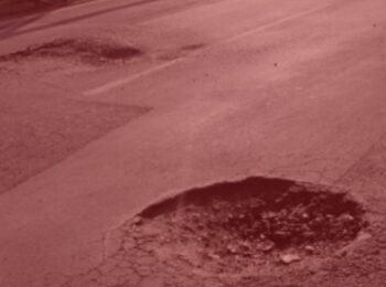Notícia: Prefeitura indenizará mulher que se acidentou em buraco na via. Na foto, uma rua com dois buracos no meio das vias. Cores na foto: vermelho e cinza.