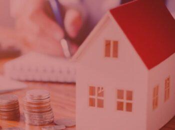 Artigo: A antecipação de herança. Imagem com fundo vermelho. Cores presentes na foto: laranja, azul, prata, dourado, amarelo e branco. Na foto, um homem assinando um papel, com algumas moedas e uma protótipo de casa em cima da mesa.