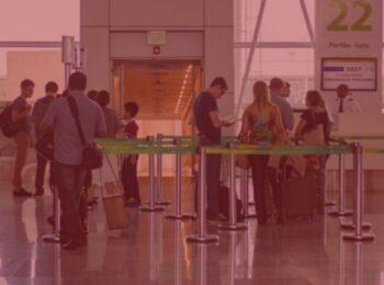 Notícia: Acordo com aéreas permite remarcação de passagens sem cobranças. #PraCegoVer: imagem com fundo vermelho, pessoas na fila de embarque no aeroporto. Cores na imagem: verde. azul, vermelho, amarelo.