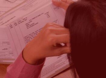 notícia: Empresa de telefonia indenizará por inscrição indevida em cadastro de inadimplentes. Na foto, uma mulher com a mão na cabeça olhando as contas para pagar que estão em cima da mesa. Cores na imagem: vermelha, branco e rosa.