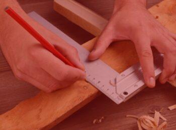 notícia: Homem será indenizado após perder dedos em acidente de trabalho. Na foto, um homem medindo uma madeira para ser cortada. Cores: vermelho, marrom, roxo e cinza.