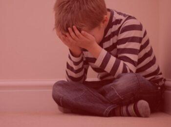notícia: Filho conquista direito de retirar sobrenome paterno após abandono afetivo. #pracegover: um menino sentado no chão com as mãos na cabeça, lamentando. Cores na imagem: vermlho, branco, azul, cinza e amarelo.