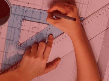 notícia: Arquiteta consegue suspender pagamentos ao FIES em razão da pandemia. #PraCegoVer: Na imagem, uma arquiteta realizando um desenho, contornando um esquadro. Cores na imagem: azul, amarelo, branco, cinza e preto.