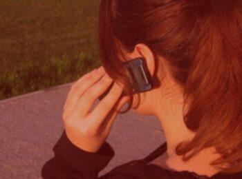 notícia: Cliente que enviou celular à assistência e nunca recebeu de volta será indenizada. #Pracegover: uma mulher sentada conversando no celular. Cores na foto: verde, preto, vermelho, amarelo e azul.