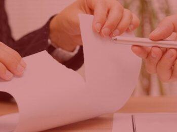 notícia: Consumidor consegue suspensão de cobranças de empreendimento que teve obras paralisadas. #pratodosverem: na foto, uma pessoa rasgando um papel que simboliza ser um contrato de negócios, e outra pessoa oferecendo uma caneta. Cores na foto: vermelho, preto, branco, cinza e verde.