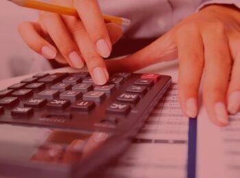 notícia: Embratel indenizará cliente em R$ 15 mil após cobrança indevida. #pratodosverem: na foto uma mulher realizando a soma das contas. Cores na foto: amarelo, preto, cinza, vermelho e roxo.