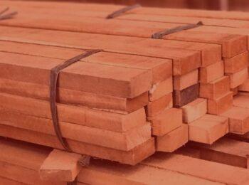 notícia: Exportadora de madeira consegue prorrogar parcelas de empréstimo devido à pandemia. #pratodosverem: madeiras de uma madeireira no depósito da empresa. Cores na foto: marrom e verde.