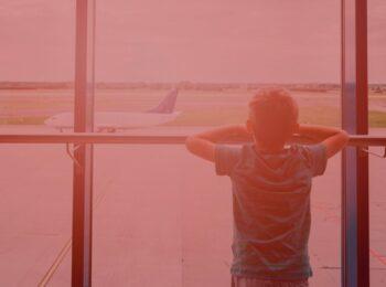 notícia: Crianças serão indenizadas por companhia aérea após pernoite em aeroporto. #pratodosverem: na foto, uma criança em um aeroporto olhando para um avião que está prestes a decolar. Cores na foto: vermelho, verde, azul, branco, cinza a preto.