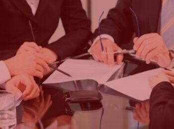 artigo: A necessidade de balanço patrimonial das quotas sociais de sociedade empresária objeto de herança. #Pratodosverem: pessoas em uma reunião simbolizando a decisão para ser tomada na empresa. Cores na foto: preto, azul, branco, amarelo e preto.