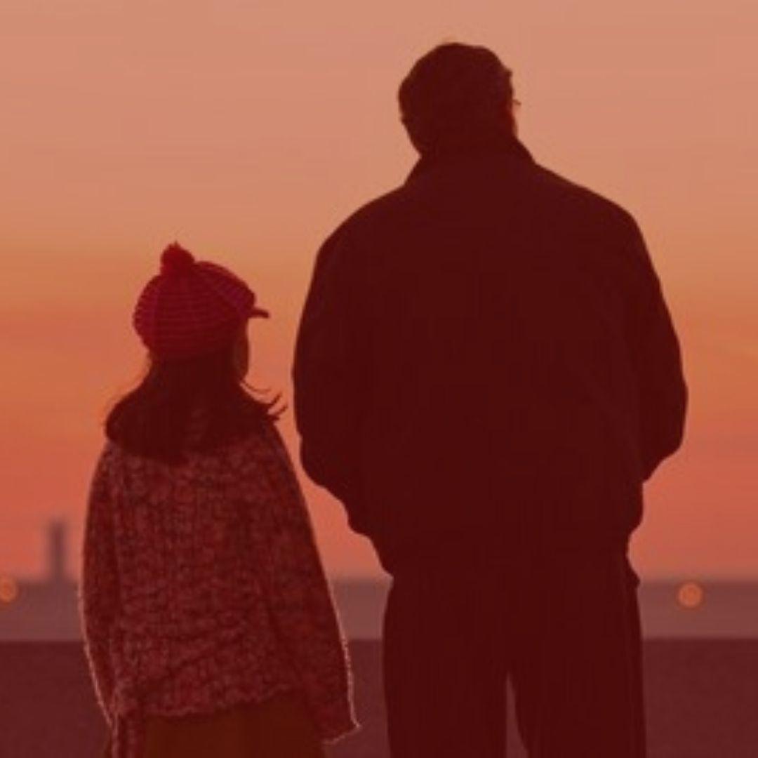 Notícia: Pai reverte decisão e poderá visitar filha durante a pandemia. #pratodosverem: pai e filha olhando a paisagem. Cores na foto: vermelho, laranja, preto .