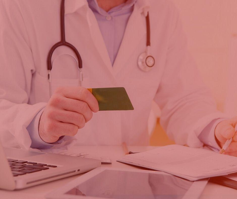 ARTIGO: As obrigações dos planos de saúde. #PRATODOSVEREM: Na foto, um médico segurando um cartão do plano de saúde enquanto realiza o atendimento. Cores na foto: Verde, branco, preto, cinza e azul.
