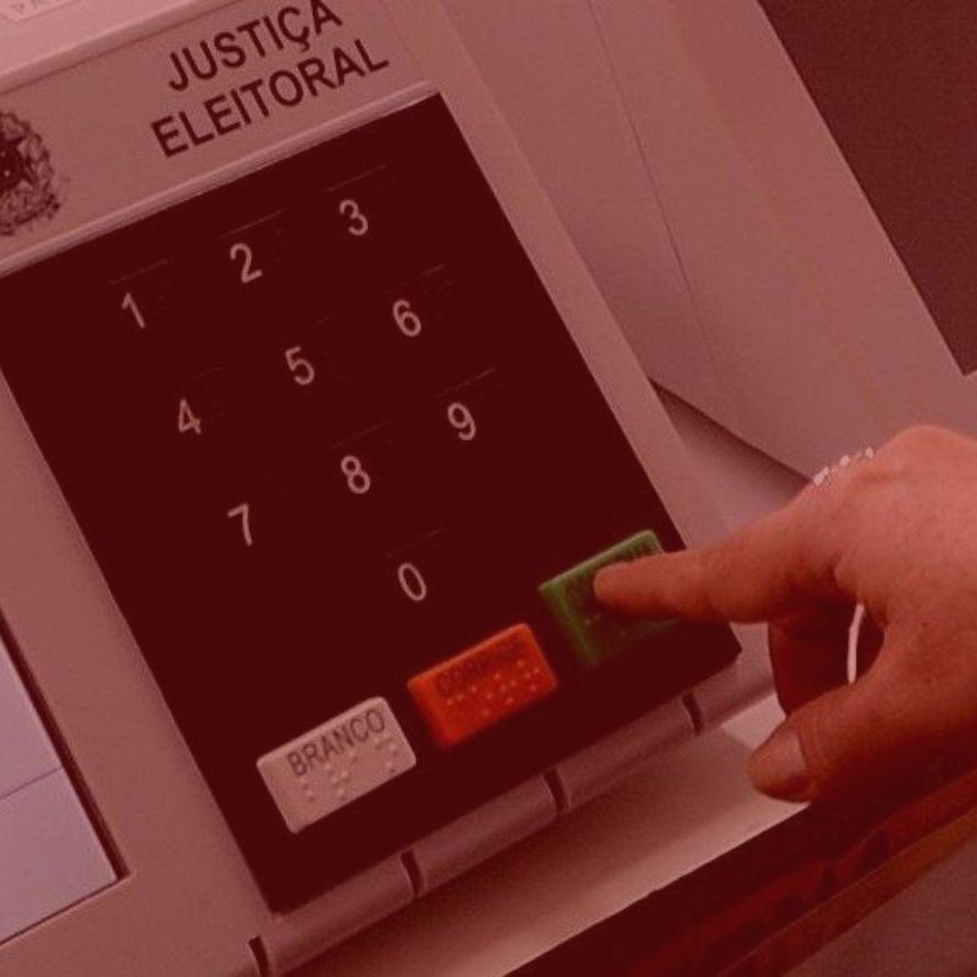 artigo: O abuso de poder e o pleito eleitoral. #pratodosverem: na foto, uma urna eleitoral e uma pessoa realizando a votação. Cores na imagem: verde, laranja, branco e preto.