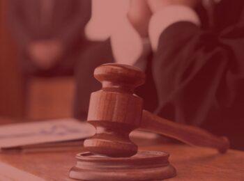 notícia: Reclamante é condenado em sucumbência por ausência injustificada em audiência. #pratodosverem: na foto, um juiz e seu martelo ao lado. Cores na foto: marrom, preto, branco e cinza.