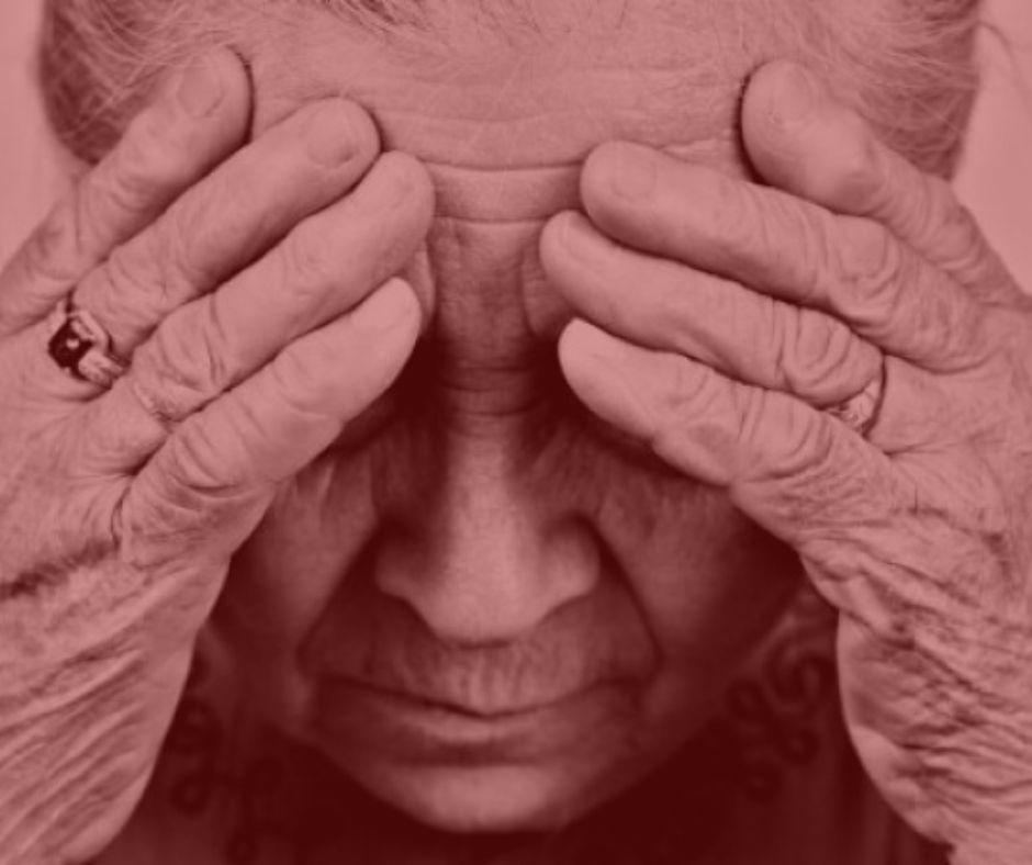 notícia: Aposentada que contratou empréstimo consignado mas sofreu desconto de cartão será indenizada. #pratodosverem: na foto, uma senhora com a mão na cabeça. Cores na imagem: vermelho e dourado.