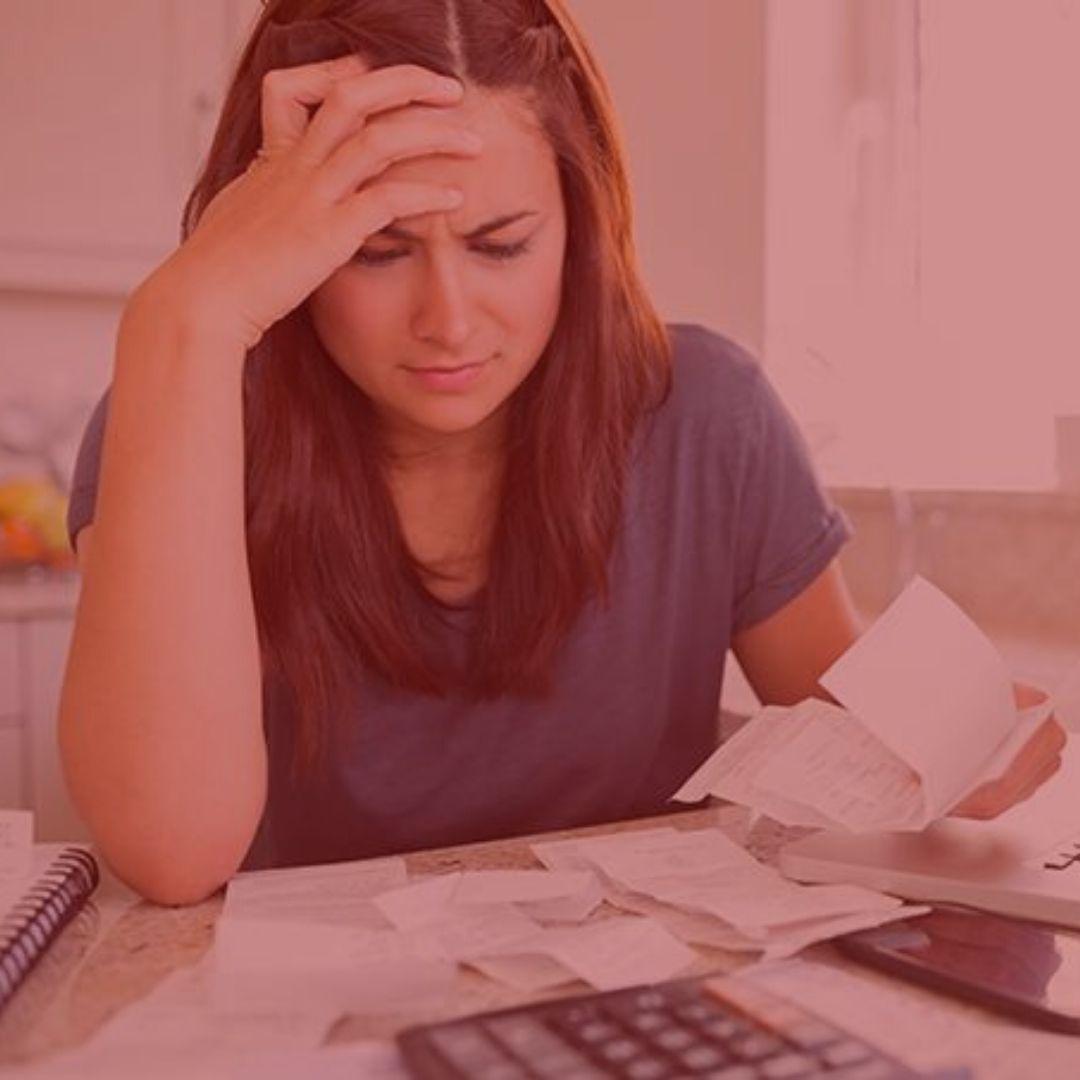 notícia: Cliente será indenizada por negativação após empresa não provar dívida de R$ 61. #pratodosverem: na foto, uma mulher olha espantada para suas contas que estão sob a mesa. Cores na foto: vermelho, branco, preto, cinza, azul, amarelo e laranja.