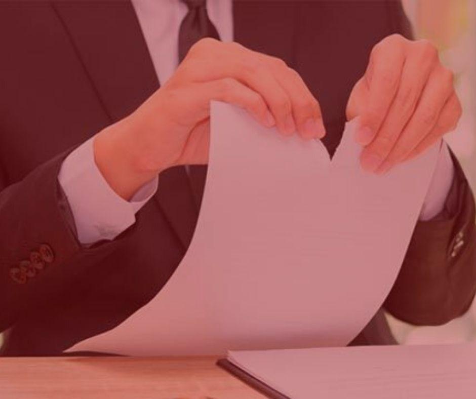 artigo: A rescisão contratual e seus acordos. #pratodosverem: na foto, um empregador rasgando um papel. Cores na foto: vermelho, preto e branco.