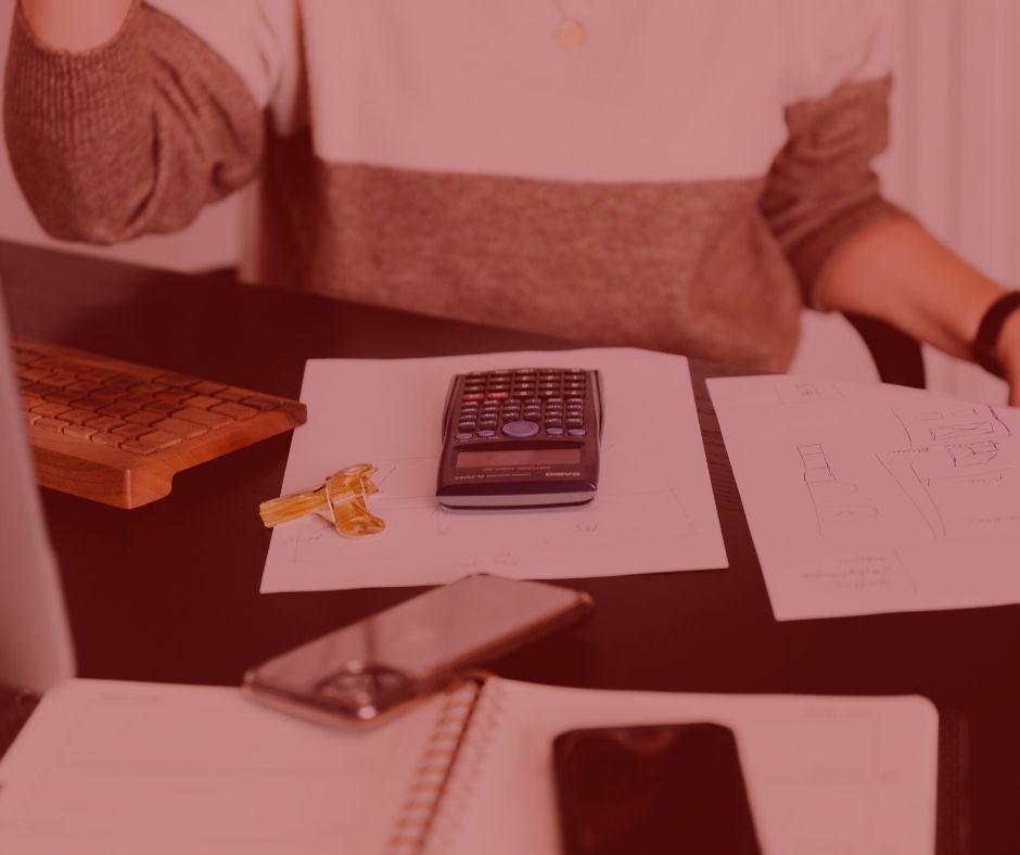 notícia: Serasa indenizará por deixar de notificar devedor de negativação. #pratodosverem: na foto, uma mulher sentada em frente a sua mesa de escritório, com uma calculadora, um celular, um computador e um papel sob a mesa. Cores na foto: cinza, branco, preto e amarelo.